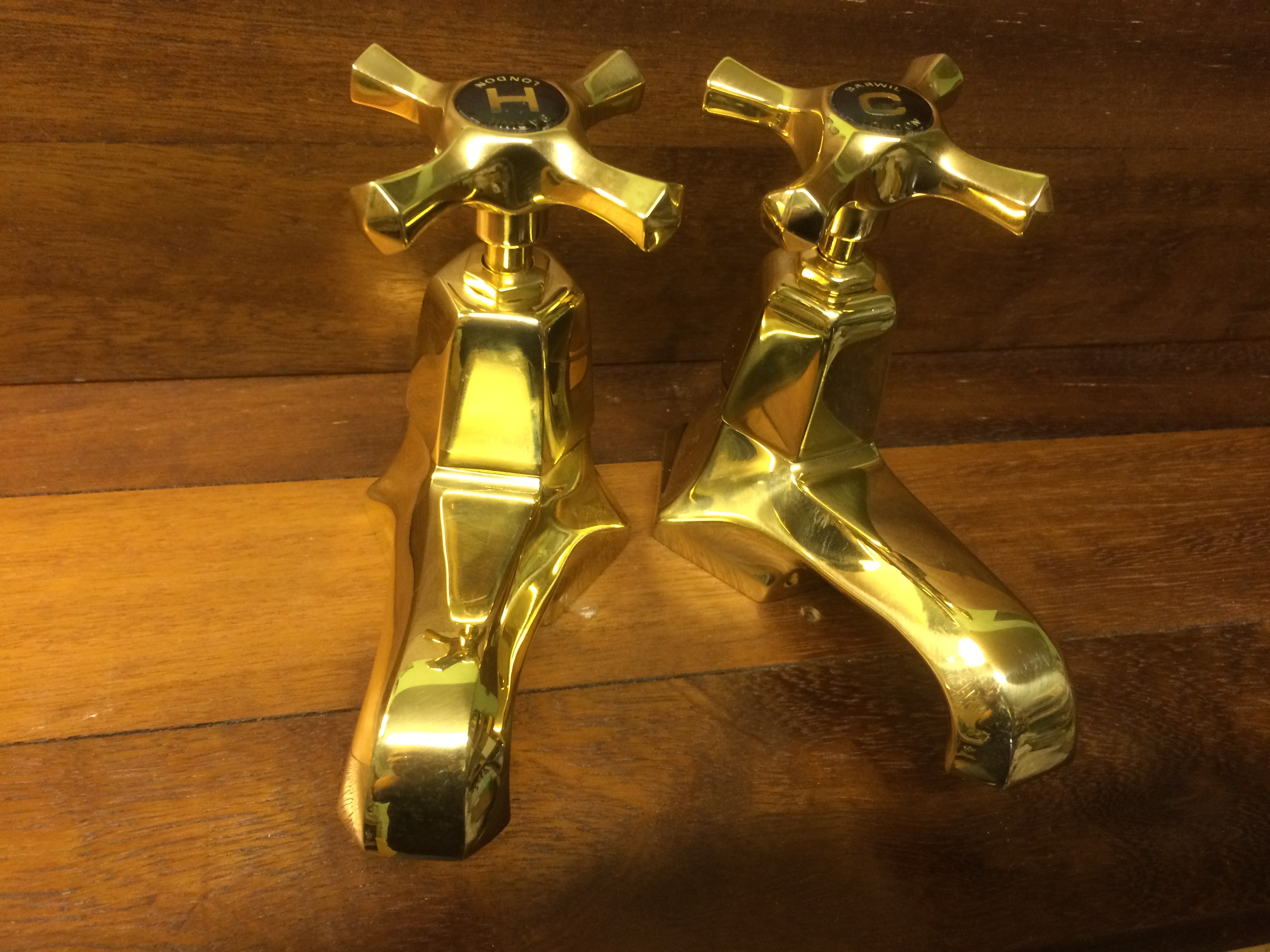 Art-Deco basin taps in polished brass.