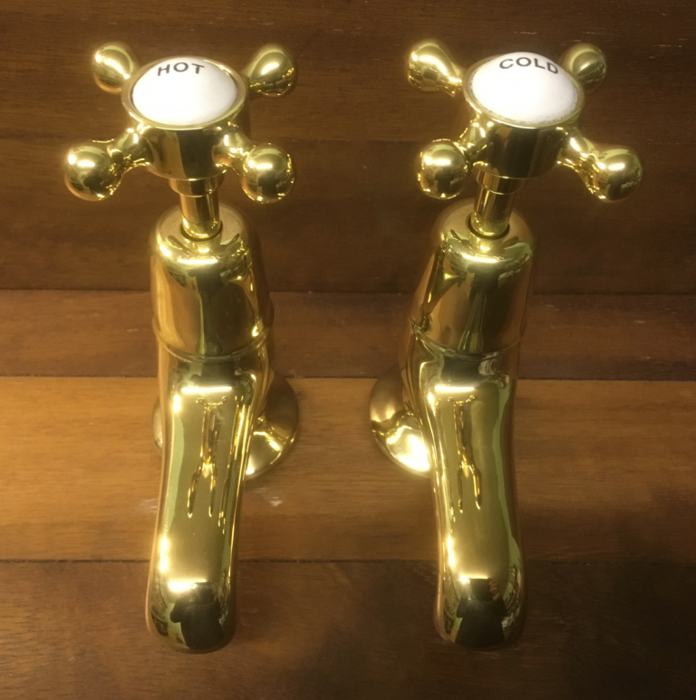 "Polished brass basin taps with 3"" spouts."