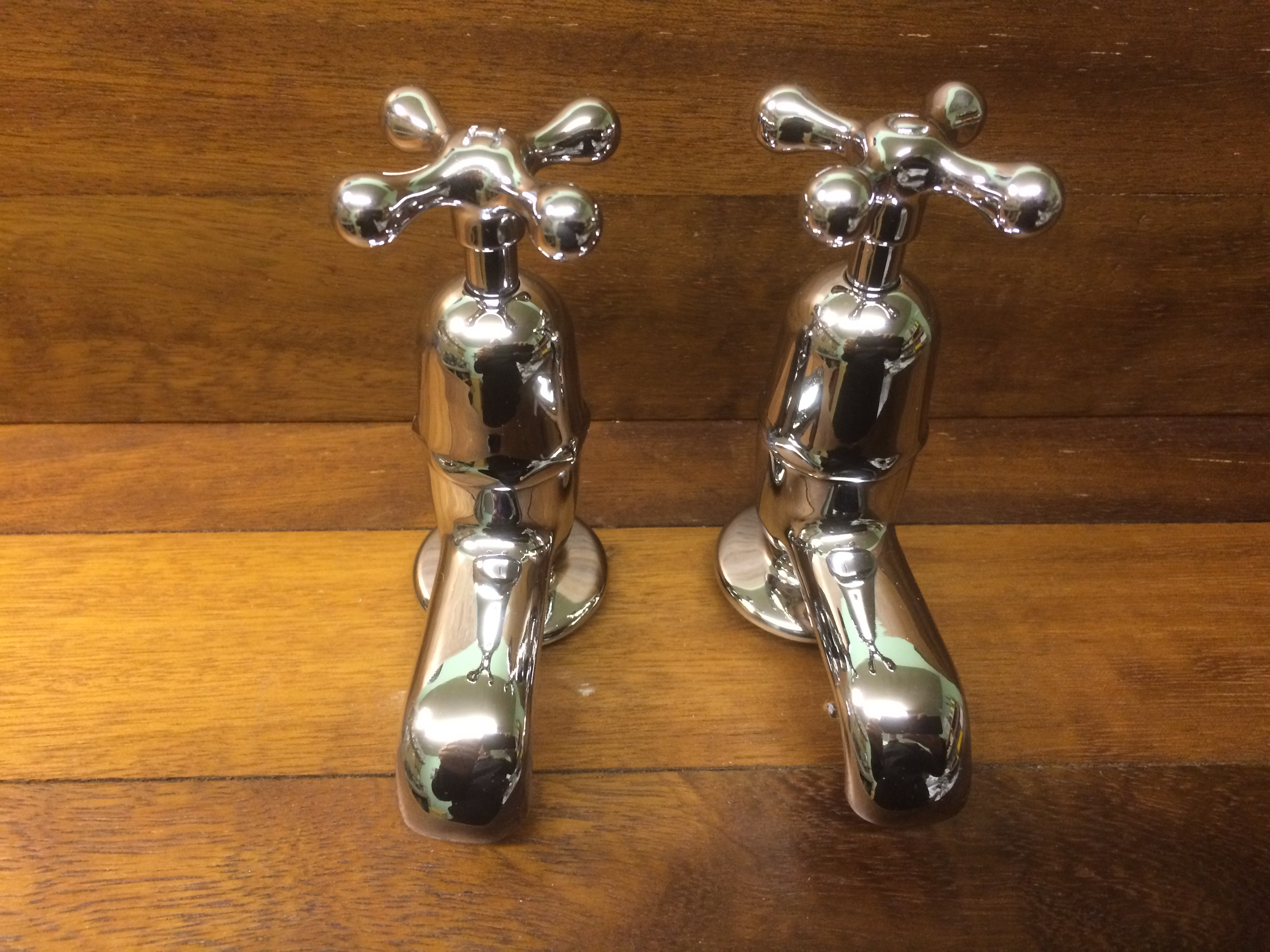 Chrome basin taps with stamped-in indicators.