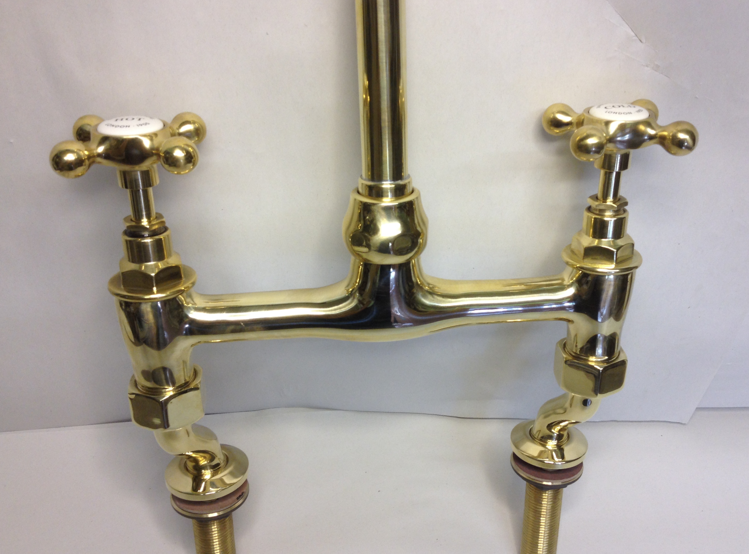 Kitchen bridge mixer taps in polished brass.